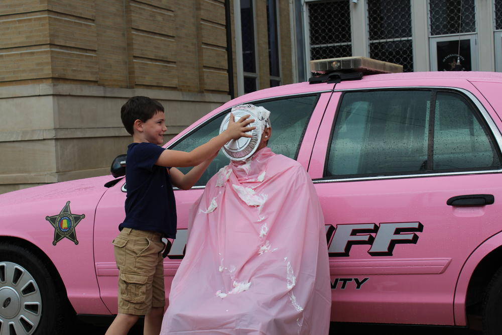 Wyatt Kervin putting pie in Sheriff Sedinger's face