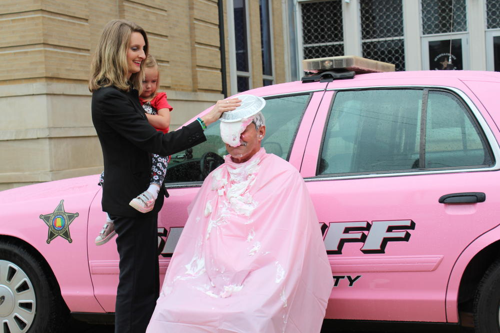 Judge Joy Booth putting a pie in Sheriff Sedinger's face
