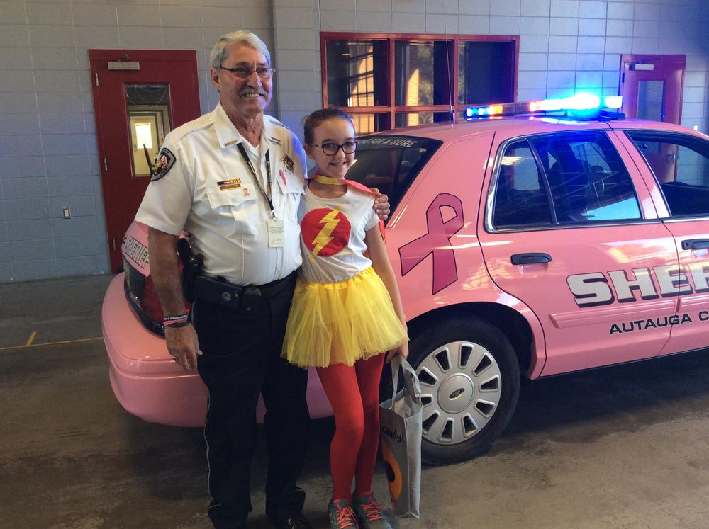 Sheriff Sedinger posing for a photo with Pink Car