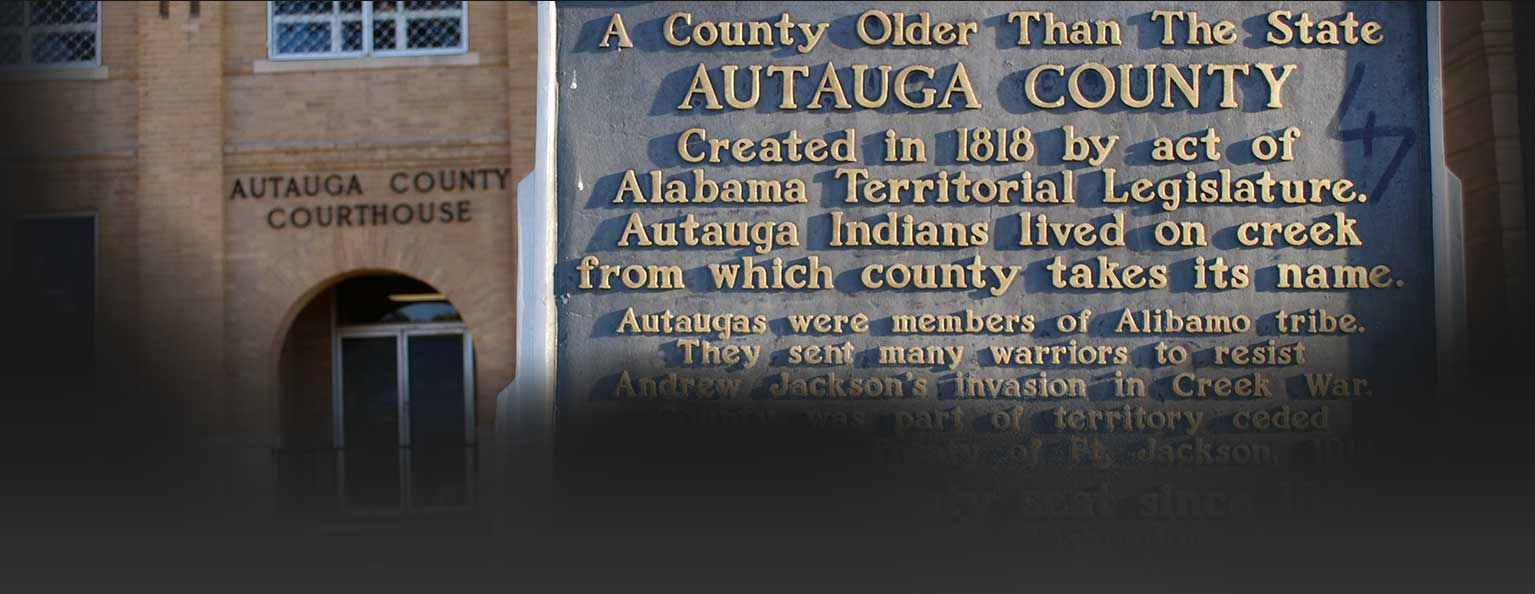 Image of autauga county court house before a plaque which reads, 'A county older than the state. Autauga county created in 1818 by act of Alabama Territorial Legislature. Atauga Indians lived on creek from which county takes its name.' More text is below this but it fades to black.